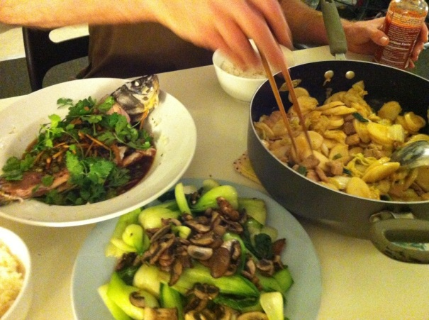 From top left: steamed fish, stir-fried sticky rice cakes, and baby bok choy with mushrooms.